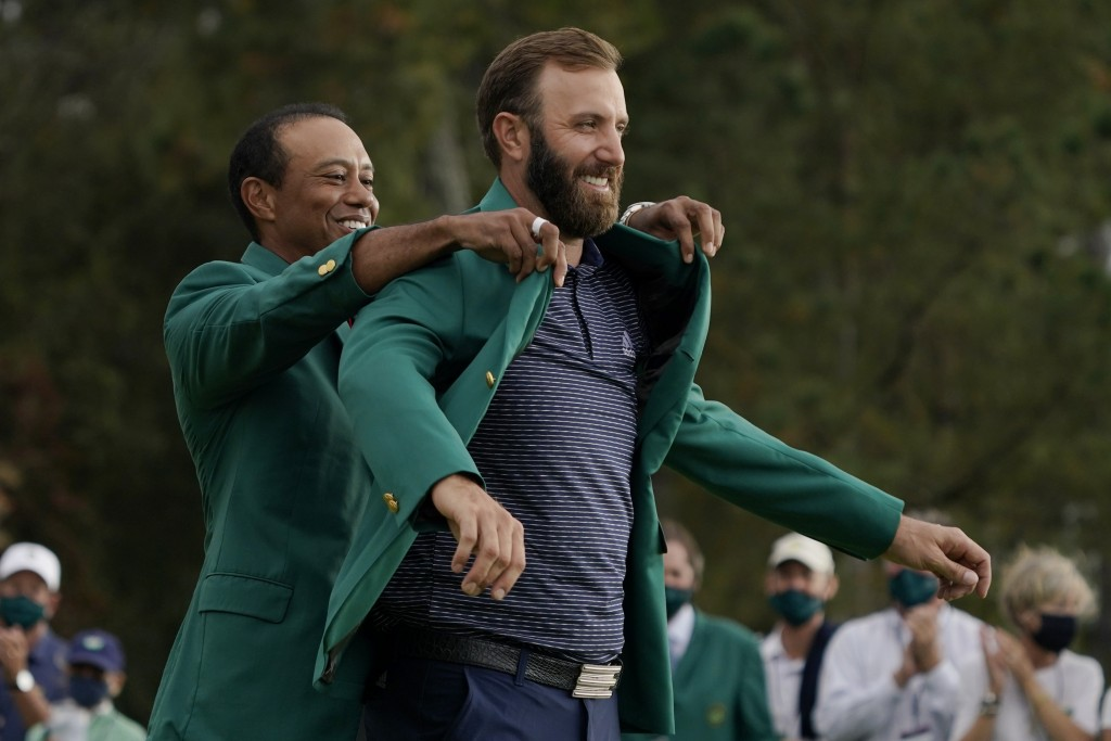 Tiger Woods helps Masters' champion Dustin Johnson with his green jacket after his victory at the Masters golf tournament Sunday, Nov. 15, 2020, in Au...