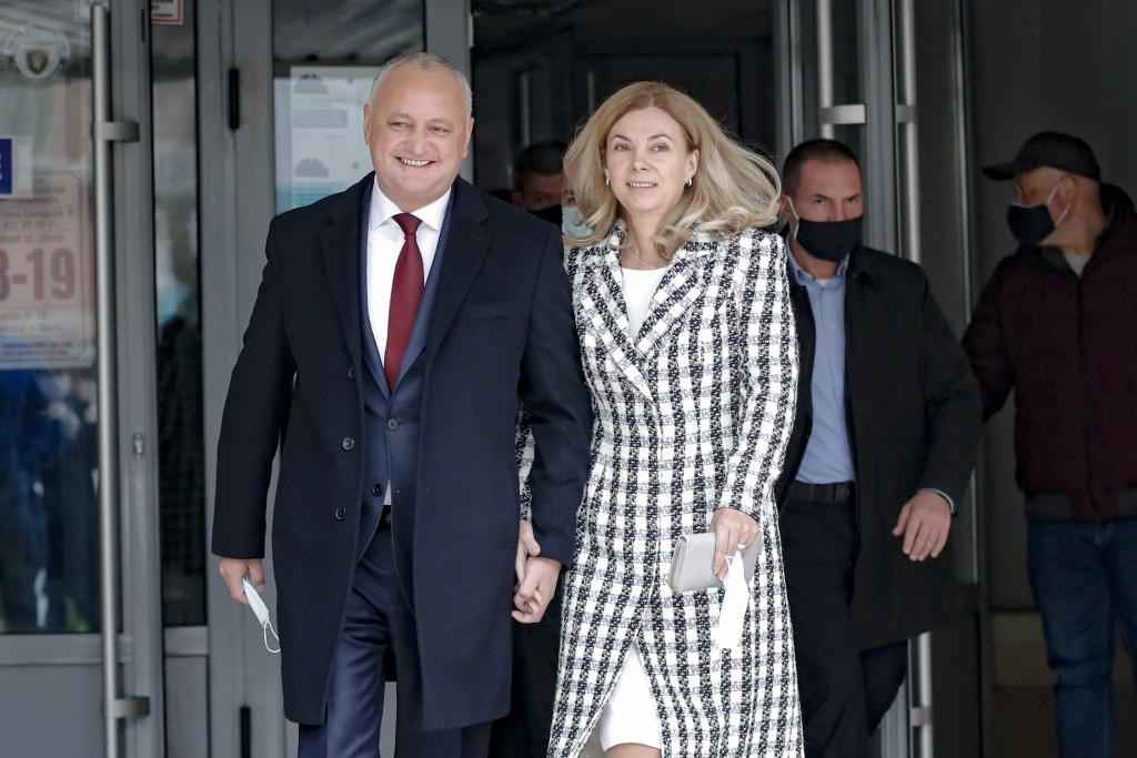 Incumbent Moldovan President Igor Dodon and his wife Galina smile while walking out of a voting station during the country's presidential election run...
