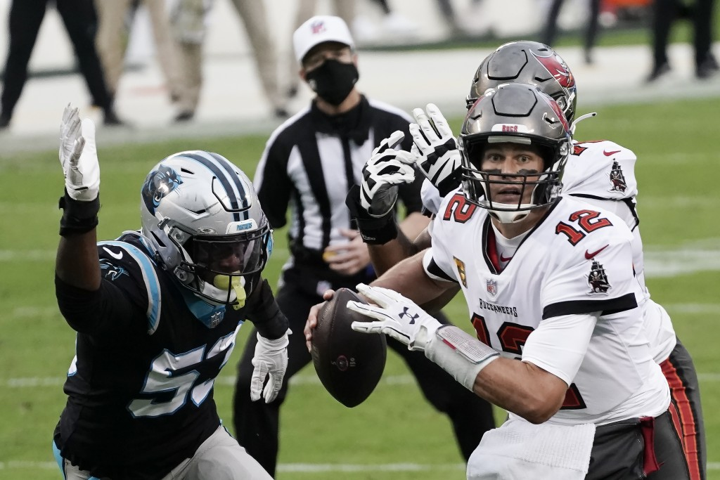 Tampa Bay Buccaneers quarterback Tom Brady (12) runs out of the pocket against Carolina Panthers defensive end Brian Burns (53) during the second half...