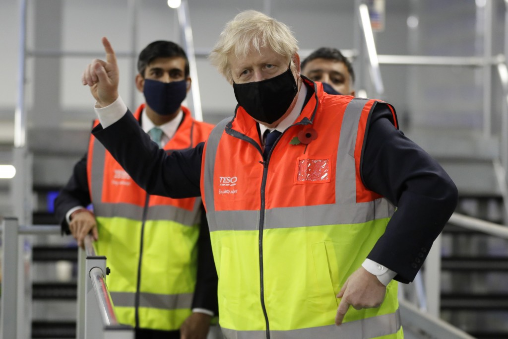 FILE - In this Nov. 11, 2020 file photo Britain's Prime Minister Boris Johnson, and Chancellor Rishi Sunak during a visit to a tesco.com distribution ...