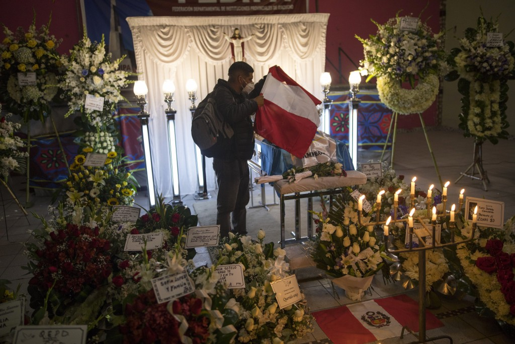 A man puts a Peruvian flag on top of the coffin of Inti Sotelo Camargo, 24, a student who was killed by the police during anti-government protests a d...