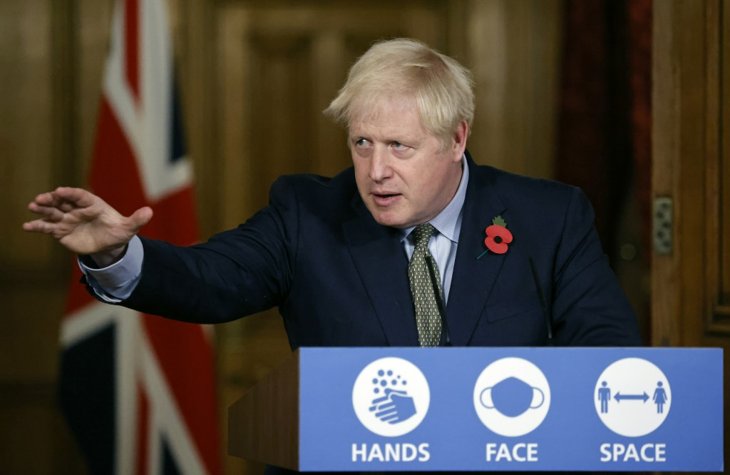 FILE - In this Nov. 9, 2020 file photo Britain's Prime Minister Boris Johnson reaches out during a virtual press conference on the coronavirus pandemi...
