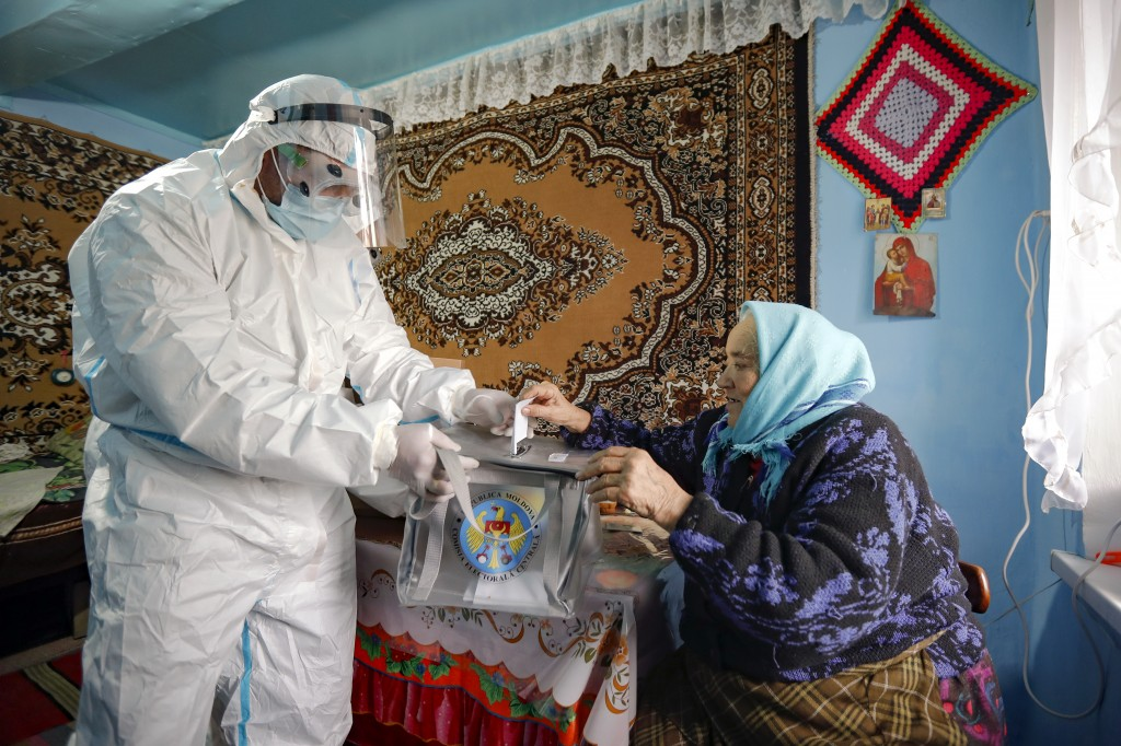 An election official wearing a biohazard suit, for protection against the COVID-19 infection, holds a mobile ballot box as an elderly lady casts her v...