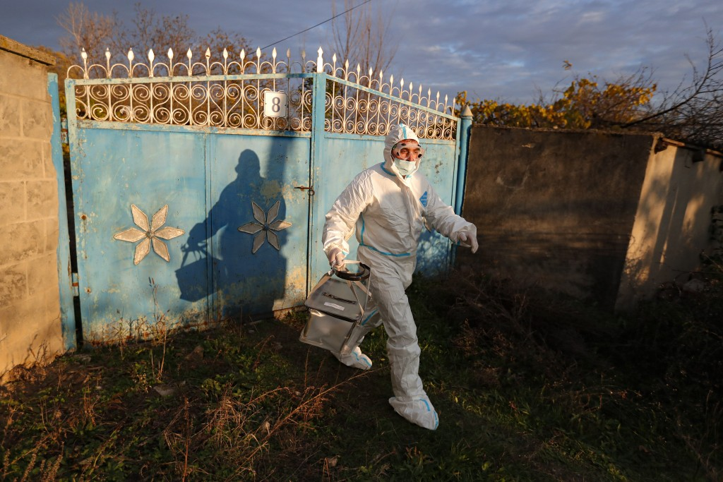 An election official wearing a biohazard suit, for protection against the COVID-19 infection, carries a mobile ballot box while visiting voters with m...