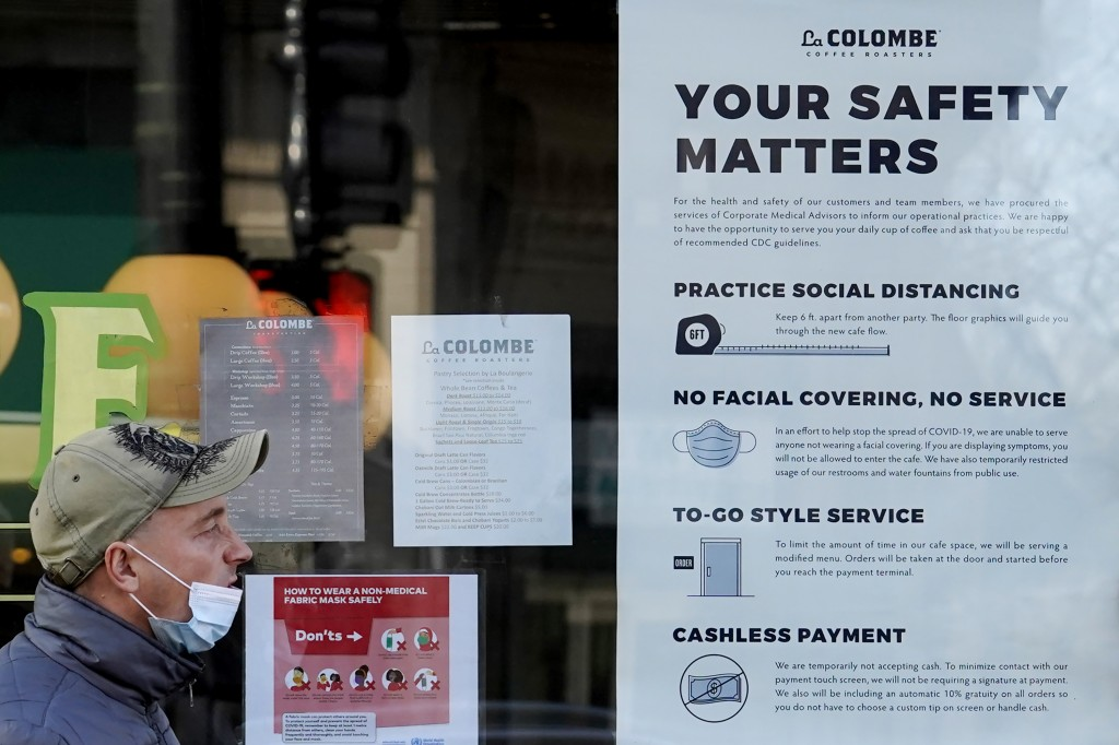 FILE - In this Nov. 12, 2020, file photo, a man walks past a coffee shop as the store displays information signs in Chicago. An increasing number of g...