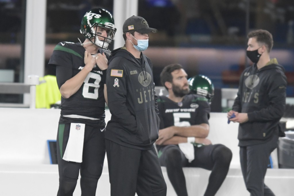 New York Jets quarterback Sam Darnold, center left, looks on from the sidelines during the first half of an NFL football game against the New England ...