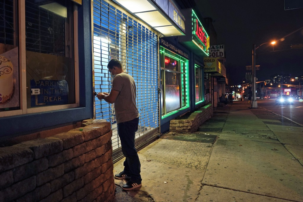 FILE - In this Nov. 12, 2020, file photo, on a mostly empty street, an employee of Justin's BBQ closes up for the night in Newark, N.J. An increasing ...