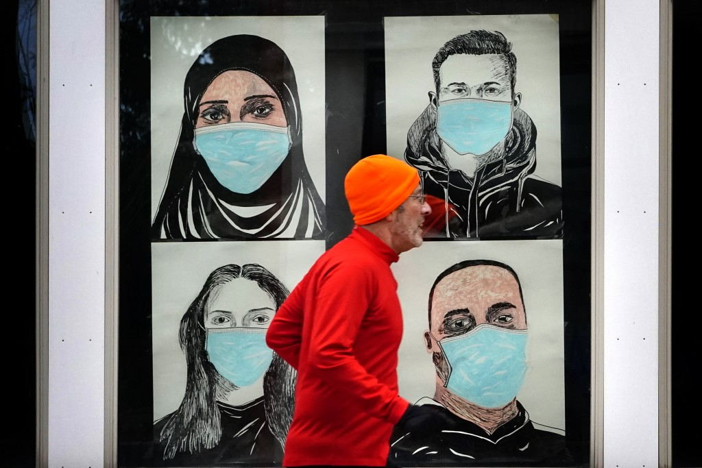 FILE - In this Nov. 16, 2020, file photo, a runner passes by a window displaying portraits of people wearing face coverings to help prevent the spread...
