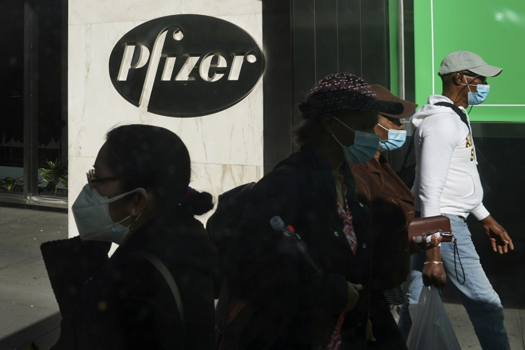 FILE - In this Nov. 9, 2020, file photo, pedestrians walk past Pfizer world headquarters in New York. Pfizer announced Wednesday, Nov. 18, 2020, more ...