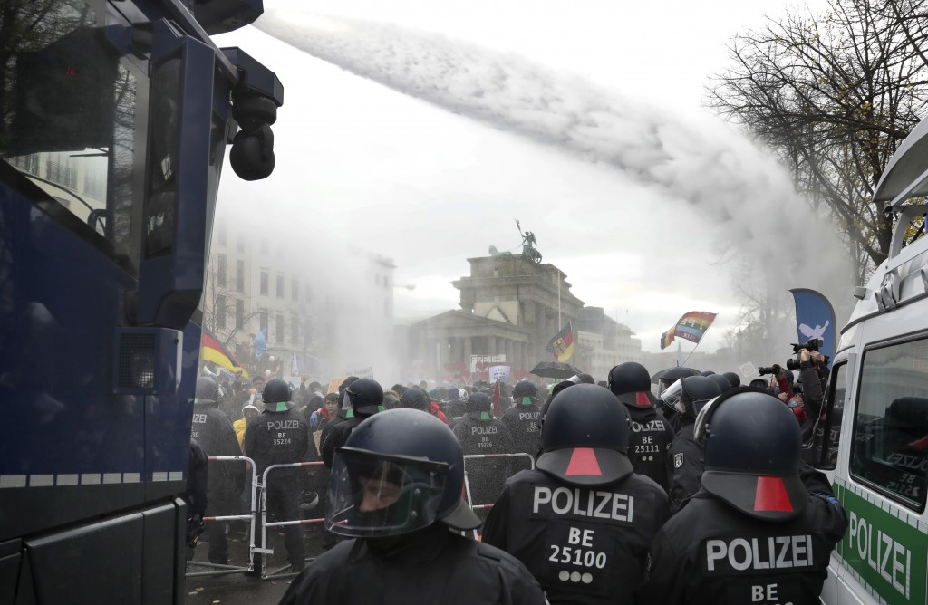Police uses water canons to clear a blocked a road between the Brandenburg Gate and the Reichstag building, home of the German federal parliament, as ...