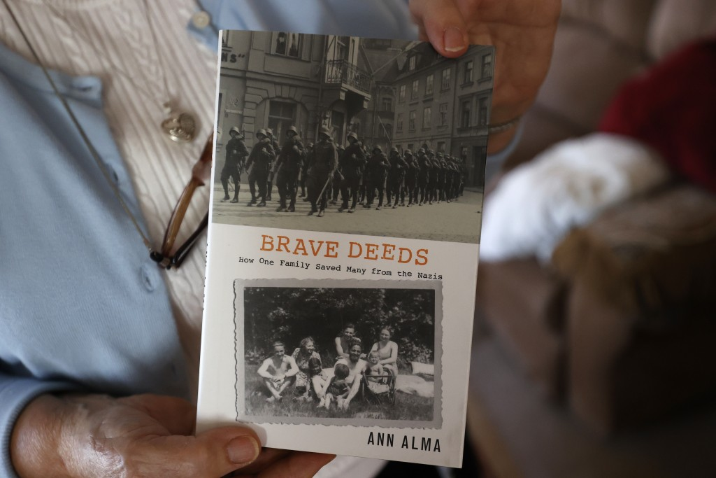 Marjan Martin Curtis holds a book about her family's rescue efforts during World War II at her home on Thursday, Nov. 12, 2020, in Spanish Fork, Utah....