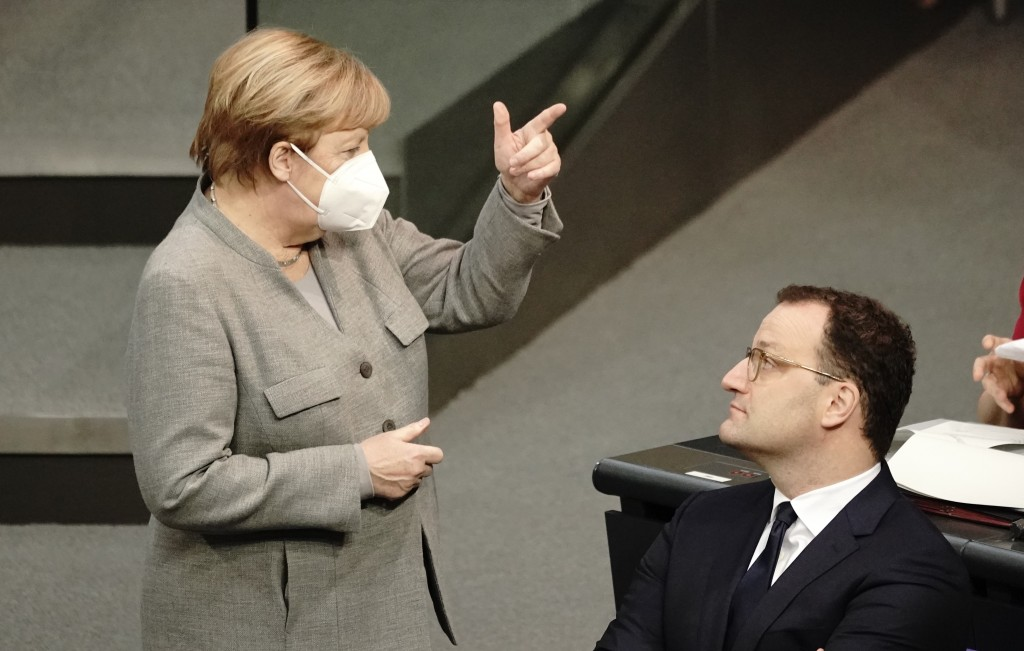 German Chancellor Angela Merkel, left, talks to German Health Minister Jens Spahn during a meeting of the German federal parliament, Bundestag, at the...