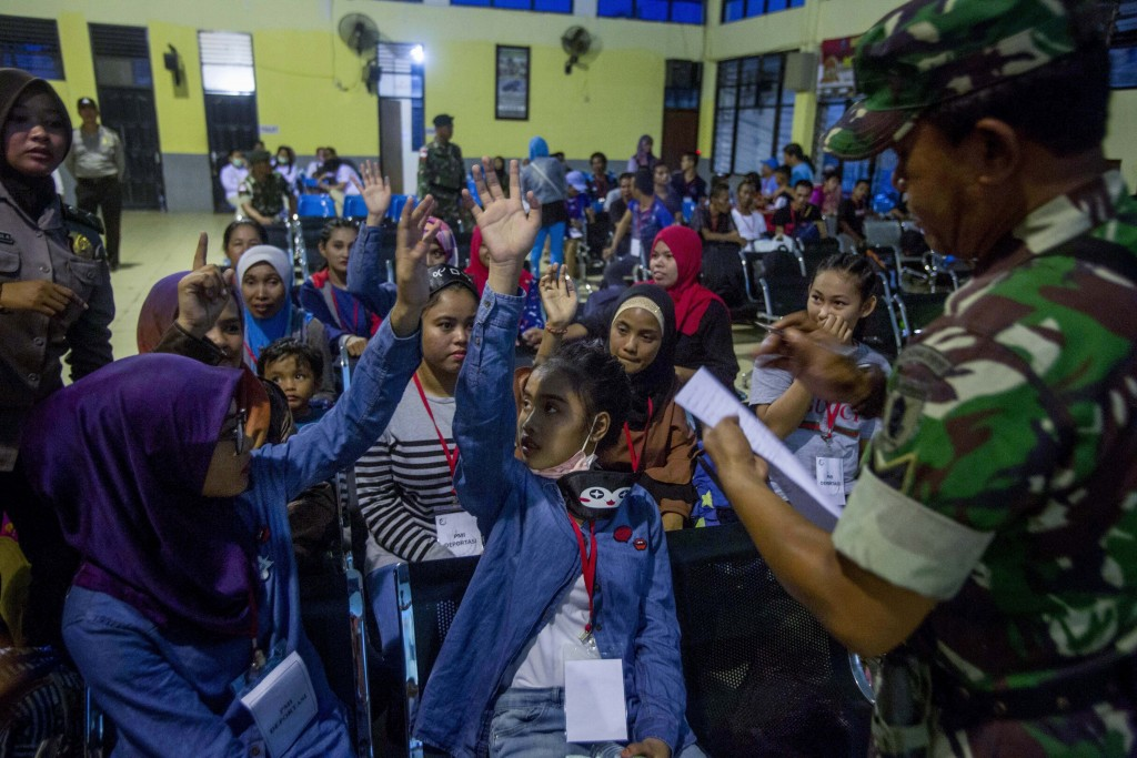 Indonesian women deported from Malaysia for working illegally, wait to be processed by Indonesian immigration officers at Nunukan, Indonesia, Thursday...