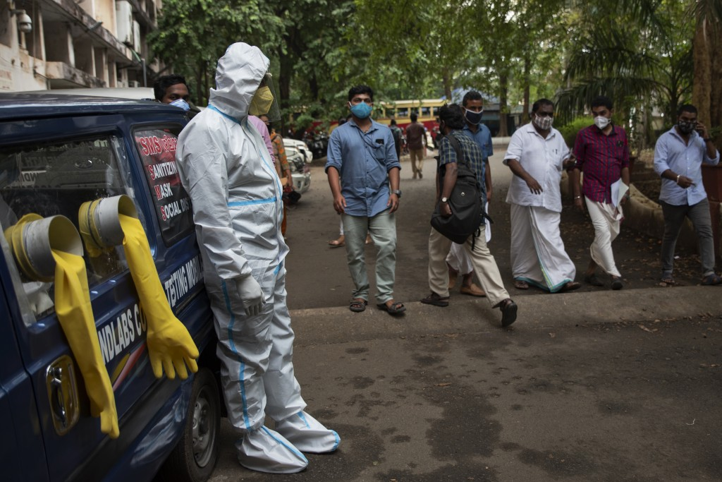 A man in protective suit stands next to a mobile COVID-19 testing kiosk outside the Ernakulam district administration headquarters in Kochi, Kerala st...