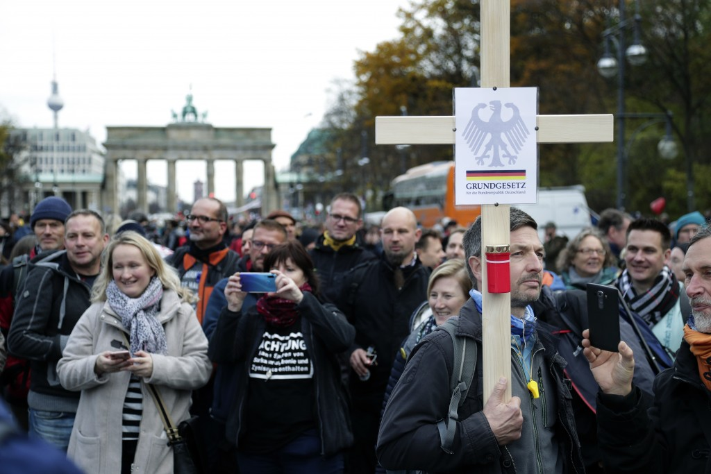 A man holds a cross with the inscription 'Constitution for the Federal Republic of Germany' as he attends a protest rally in front of the Brandenburg ...