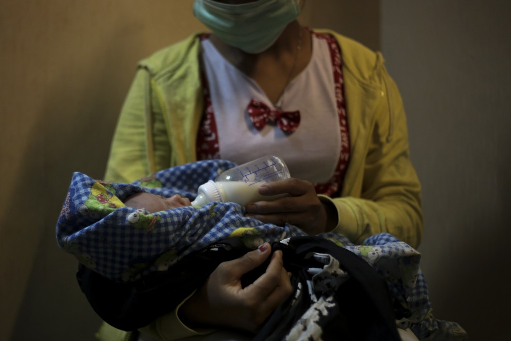A 17-year-old mother gives a bottle to her 2-week-old baby, whom she says was born as a result of a rape in Sumatra, Indonesia, Sunday, Sept. 9, 2018....