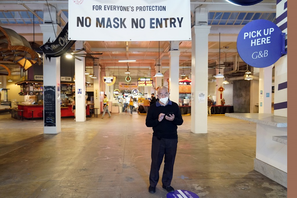 FILE - In this Nov. 16, 2020, file photo, a sign points to a mask mandate at the Grand Central Market in Los Angeles. Gov. Gavin Newsom announced Mond...