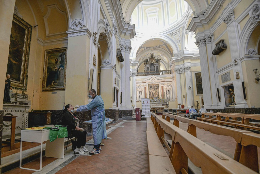 A medical operator performs COVID-19 test swabs in the Church of San Severo Outside the Walls, in the heart of Naples, Italy, Wednesday, Nov. 18, 2020...