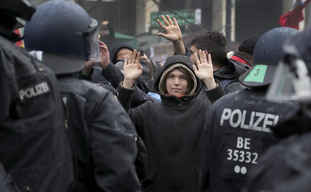 A protestor lifts her hands as police officers block a road between the Brandenburg Gate and the Reichstag building, home of the German federal parlia...