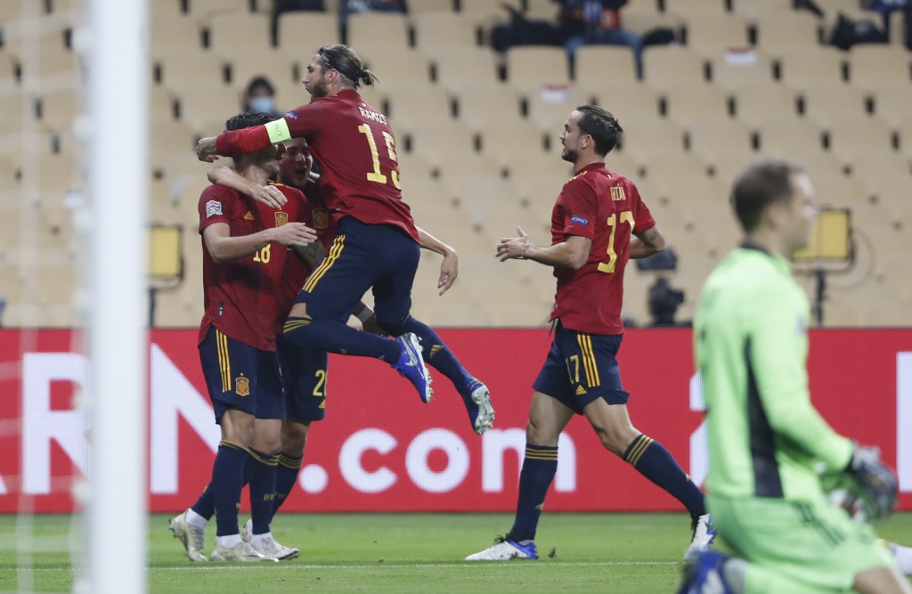 Spain's captain Sergio Ramos, center, celebrates with scorer Ferran Torres, left, during the UEFA Nations League soccer match between Spain and German...