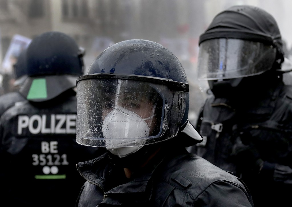 A police person wears a face mask under a helmet after beeing hit by a water canon during a violent protest ralley in a road between the Brandenburg G...