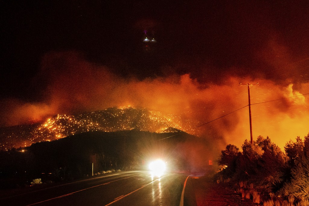 A car drives along Highway 395 as the Mountain View Fire tears through the Walker community in Mono County, Calif., on Tuesday, Nov. 17, 2020. (AP Pho...
