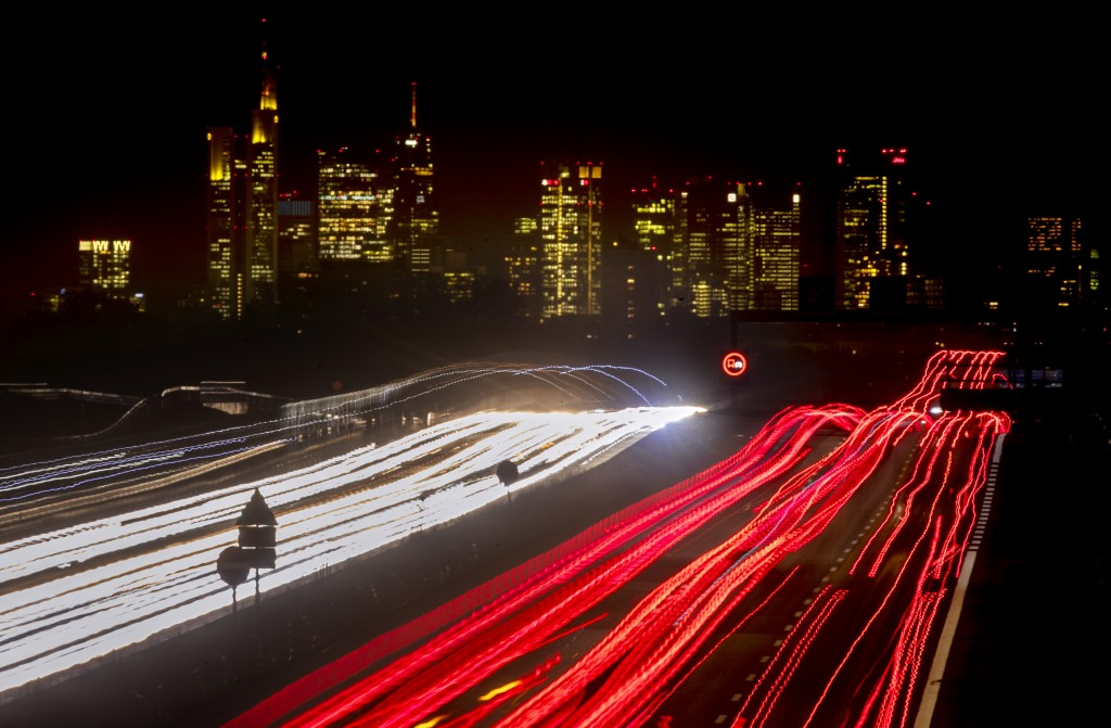 A long time exposure photo shows cars and trucks driving on a highway near Frankfurt, Germany, Tuesday, Nov. 17, 2020. In background the buildings of ...