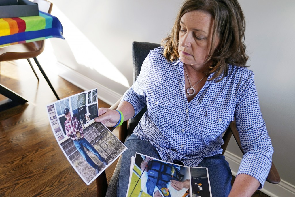 June Linnertz poses with photos of her father at her Chaska, Minn., home, Wednesday, Nov. 11, 2020. Her father, James Gill, 78, died of Lewy Body Deme...