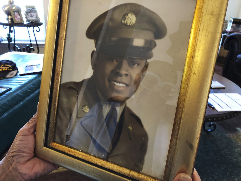 Barbara Leak-Watkins is reflected in a photo of her late father, Alex Leak Jr., at her home in Greensboro, N.C., on Wednesday, Nov. 4, 2020. The Army ...