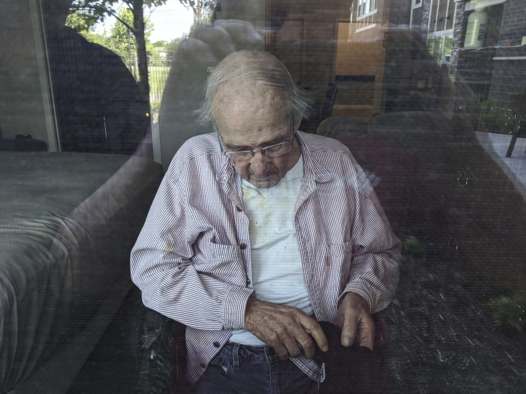 This June 7, 2020, photo provided by June Linnertz shows her father, James Gill, seen through a window at Cherrywood Pointe nursing home in Plymouth, ...