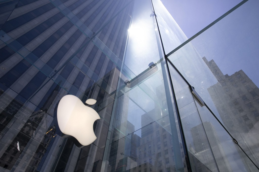 FILE - In this June 16, 2020, file photo, the sun is reflected on Apple's Fifth Avenue store in New York. Apple will cut its app store fee in half fro...