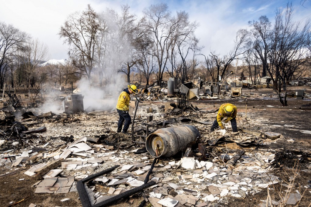 Firefighters Emiliano Saldivar, left, and Chris Martinez sift through debris to recover keepsakes for residents after the Mountain View Fire tore thou...