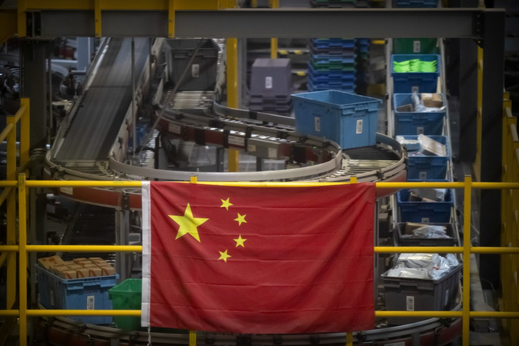 FILE - In this Nov. 11, 2020, file photo a Chinese flag hangs near an automated parcel handling line at a warehouse for an online retailer in Beijing....