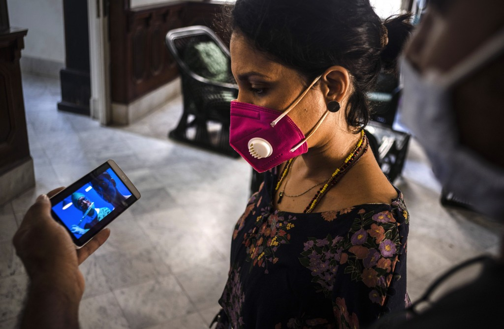 Wearing a mask to curb the spread of the new coronavirus, Cuban singer and composer Haydee Milanes watches a music video on a partner's mobile phone i...