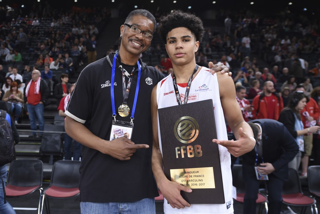 Cholet's Killian Hayes holds his trophy and poses with his father, DeRon, a former basketball player, during the French Cup under-17 final between Cho...
