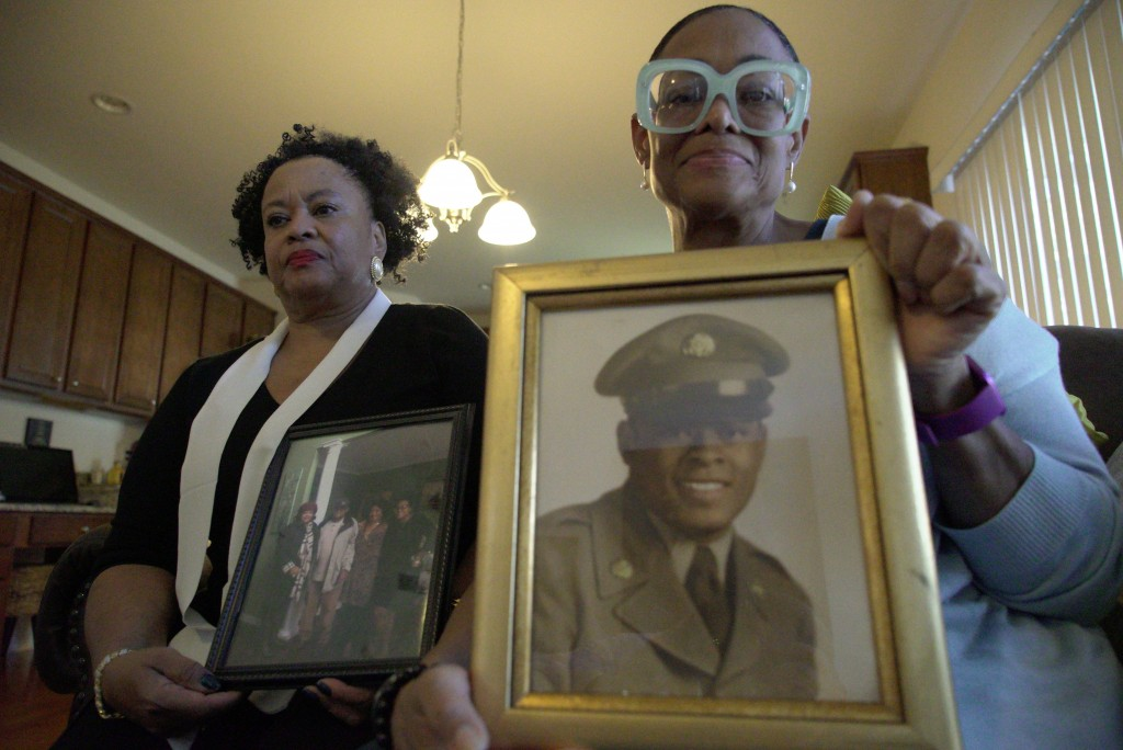 Sisters Barbara Leak-Watkins, right, and Alberta Lynn Fantroy pose with photos of their late father, Alex Leak Jr., at Watkins' home in Greensboro, N....