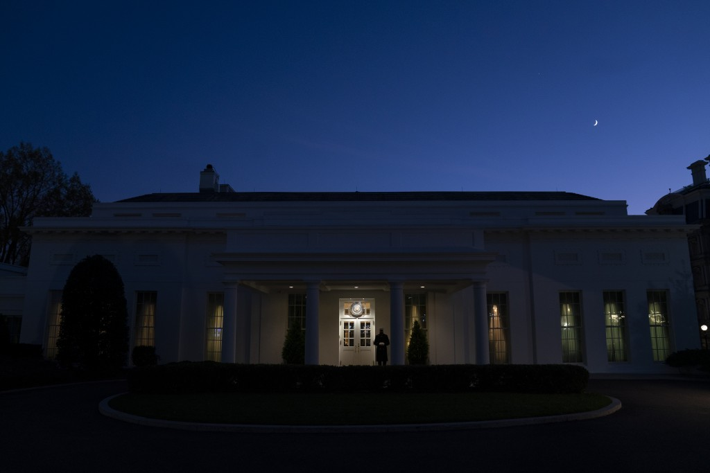 A Marine stands outside the entrance to the West Wing of the White House, signifying that President Donald Trump is in the Oval Office, Wednesday, Nov...