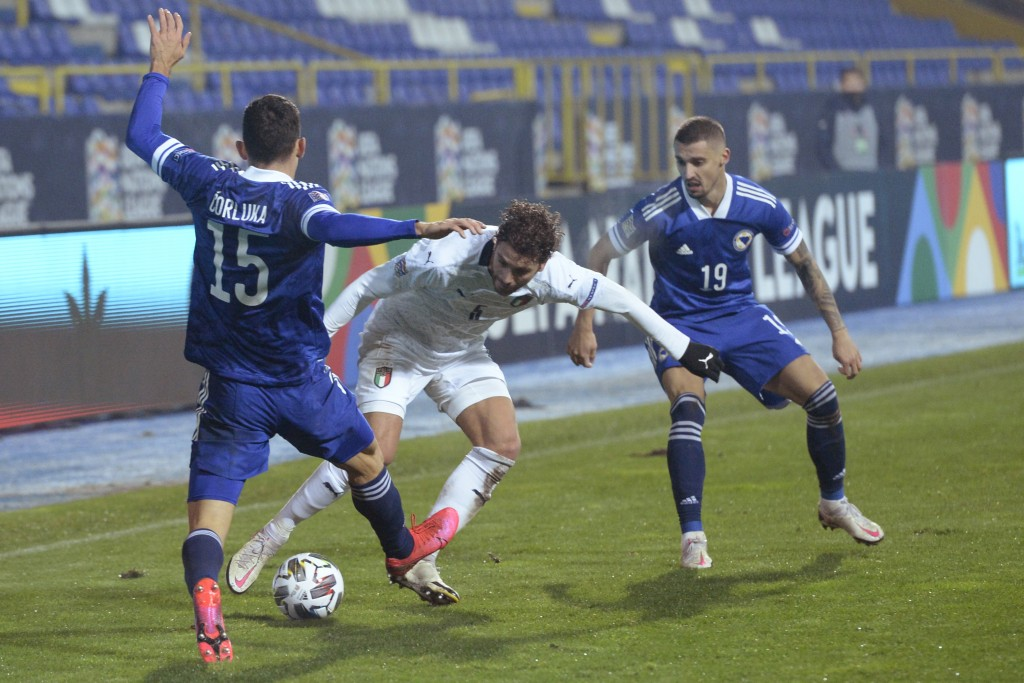 Italy's Manuel Locatelli, center, is challenged by Bosnia's Josip Corluka, left, during the UEFA Nations League soccer match between Bosnia and Italy,...