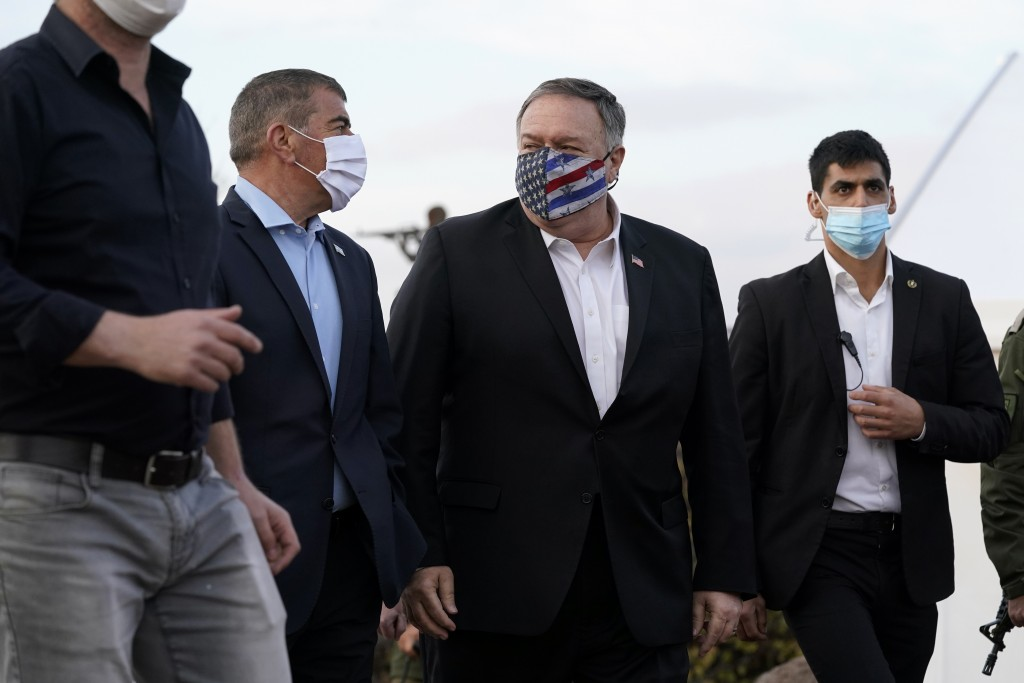 Secretary of State Mike Pompeo walks with Israel's Foreign Minister Gabi Ashkenazi, left, after a security briefing on Mount Bental in the Israeli-con...