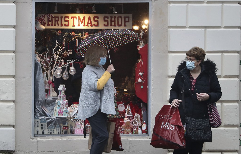 People wearing face coverings outside a Christmas Shop in Stirling, Scotland, Friday Nov. 20, 2020. This shop will close later Friday along with other...