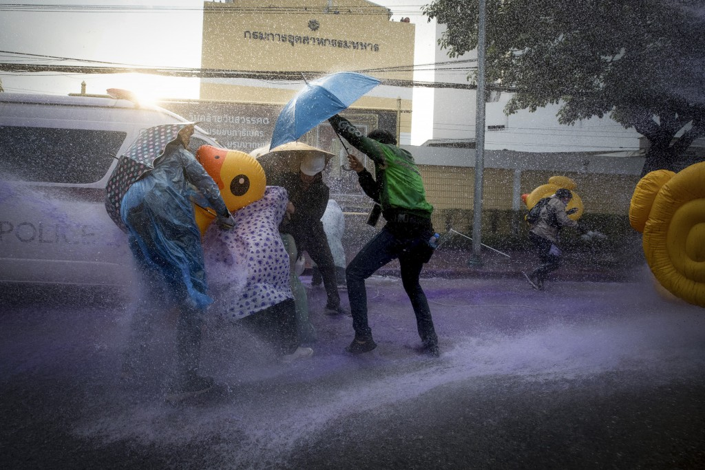 Pro-democracy protesters take cover with inflatable ducks and umbrellas as police fire water cannons during an anti-government rally near the Parliame...