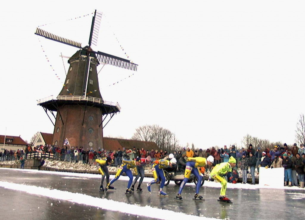 FILE - In this Saturday, Jan. 4, 1997, file image, skaters pass a windmill at the village of Birdaard, northern Netherlands, during the Elfstedentocht...