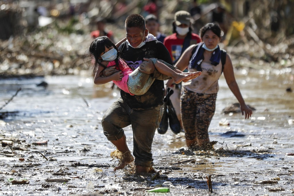 A man carries a girl through debris and floods in the typhoon-damaged Kasiglahan village in Rodriguez, Rizal province, Philippines, Friday, Nov. 13, 2...