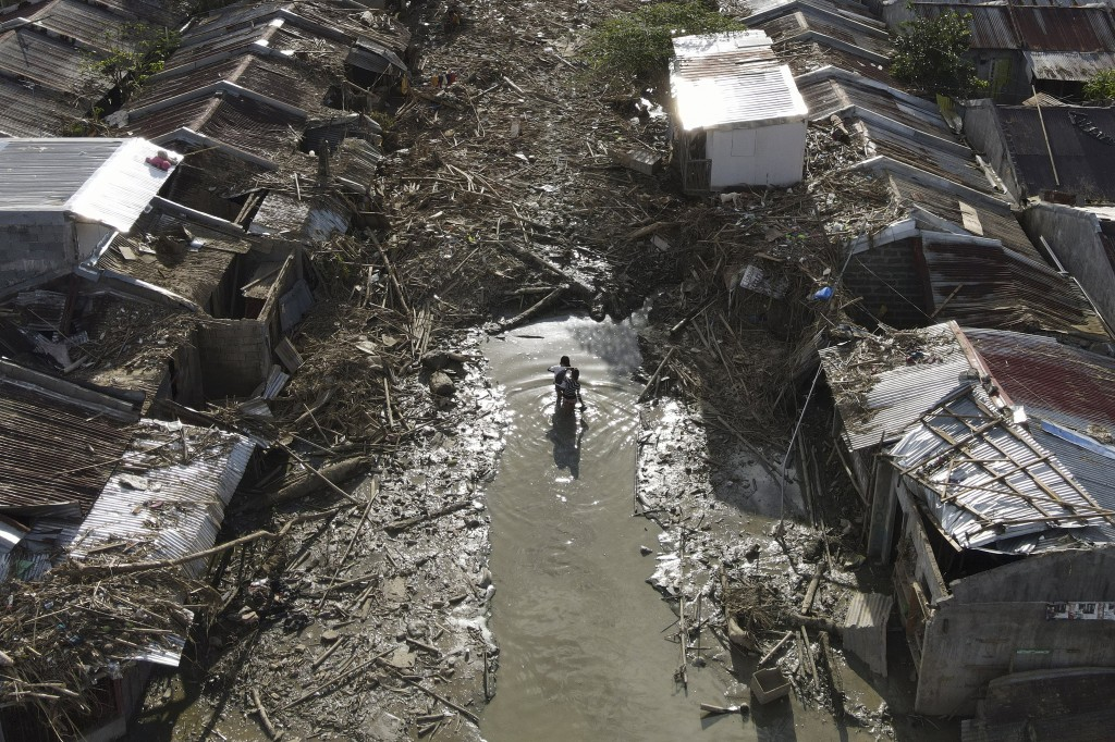 Two residents walk along a path of mud and debris towards their village damaged by Typhoon Vamco in Rodriguez, Rizal province, Philippines, Tuesday, N...