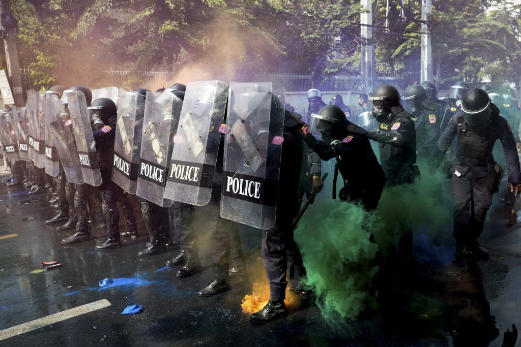 Police in riot gear stand in formation as pro-democracy protesters throw smoke bombs near the Parliament in Bangkok, Tuesday, Nov. 17, 2020. Thailand'...