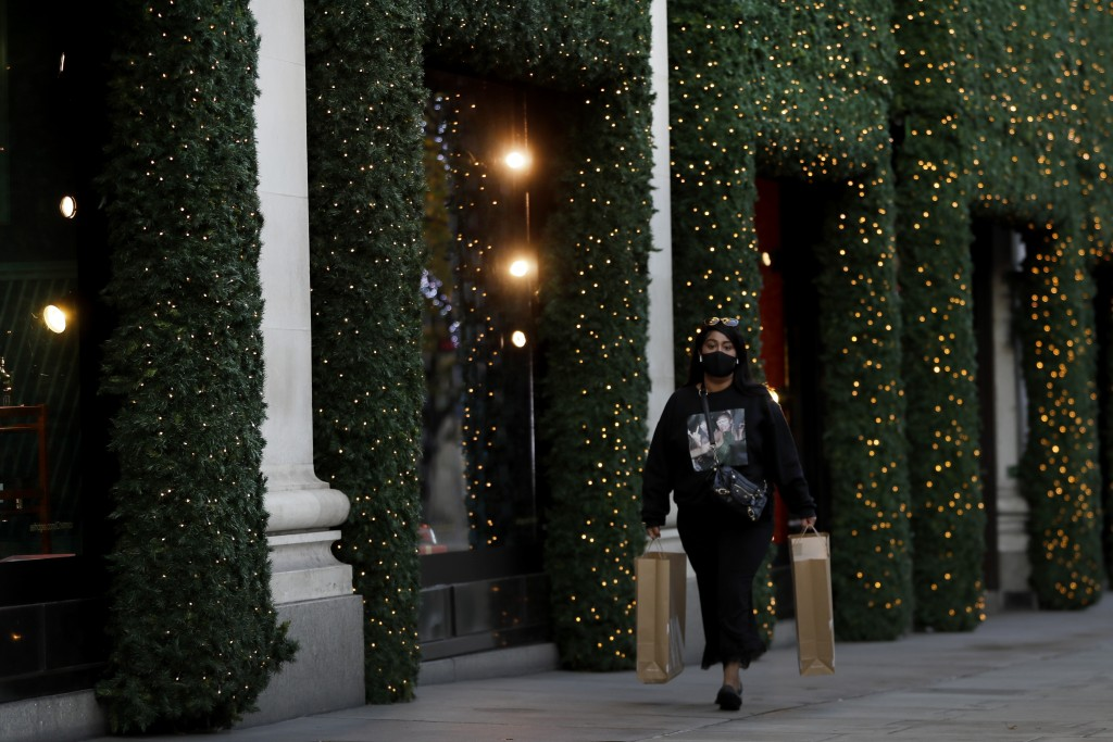 A woman walks past Christmas decorations on Oxford Street during a second lockdown in London, Thursday, Nov. 19, 2020. Businesses that have been force...