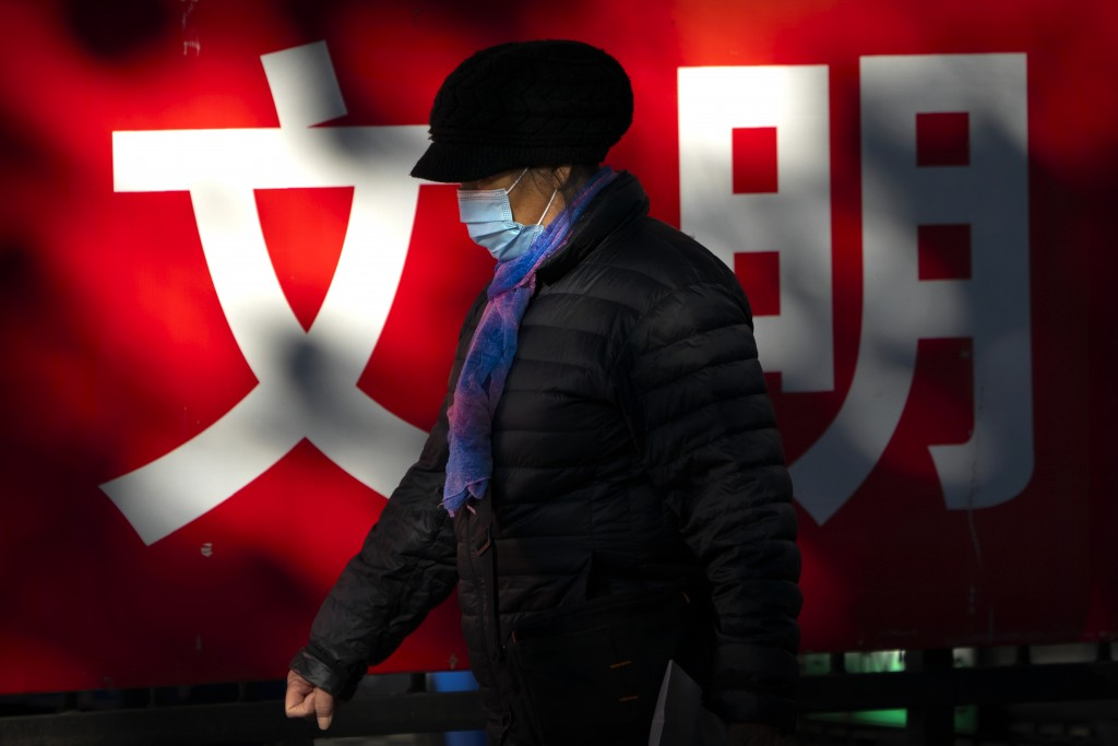 "A woman wearing a face mask to protect against the coronavirus walks past a propaganda billboard with the characters for ""culture"" in Beijing, Friday,..."