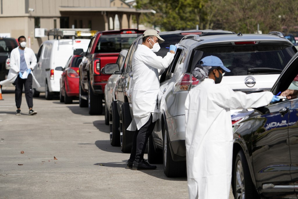 Healthcare workers process people waiting in line at a United Memorial Medical Center COVID-19 testing site Thursday, Nov. 19, 2020, in Houston. Texas...