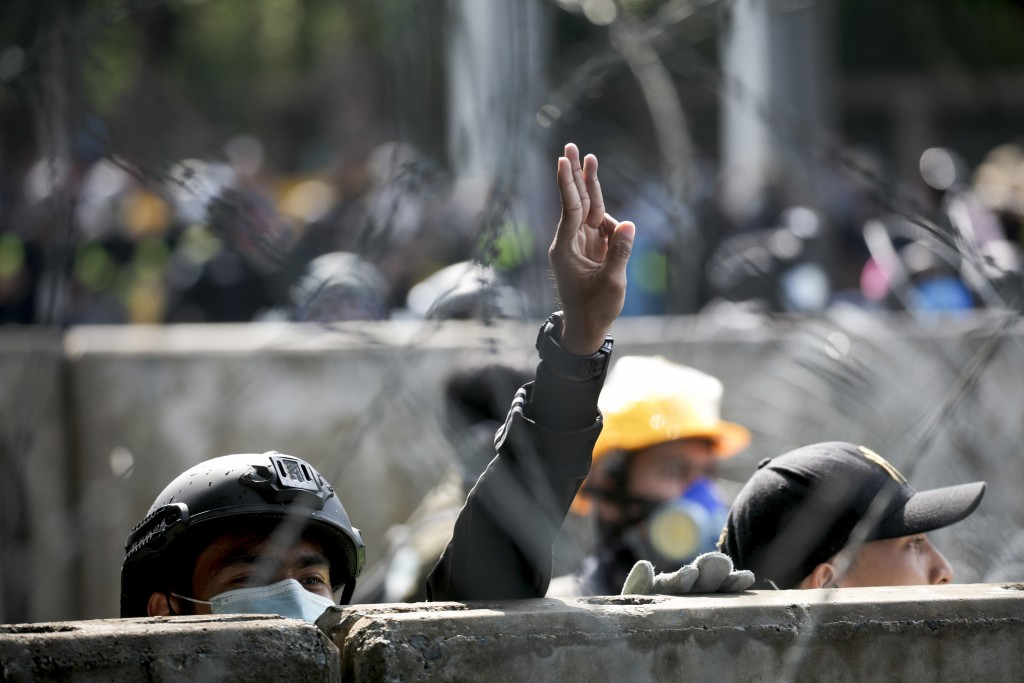 A pro-democracy protester flashes the three-finger protest gesture near the Parliament in Bangkok, Tuesday, Nov. 17, 2020. Thailand's political battle...