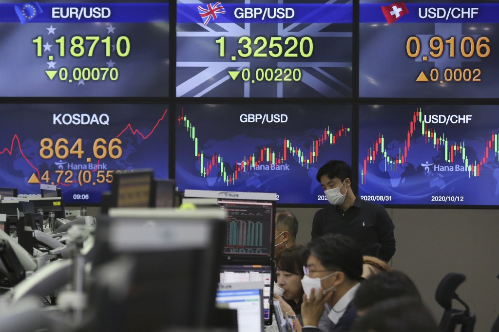 A currency trader watches monitors at the foreign exchange dealing room of the KEB Hana Bank headquarters in Seoul, South Korea, Friday, Nov. 20, 2020...